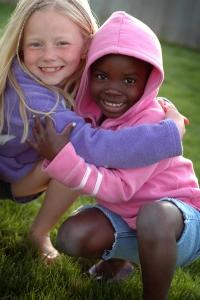 AA ISTOCK - AA girl and C girl hugging