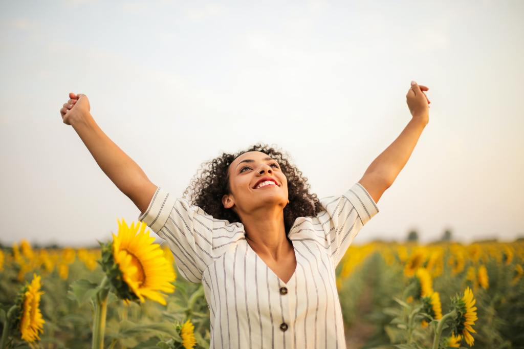 Woman smiling triumphantly in a sunflower field.