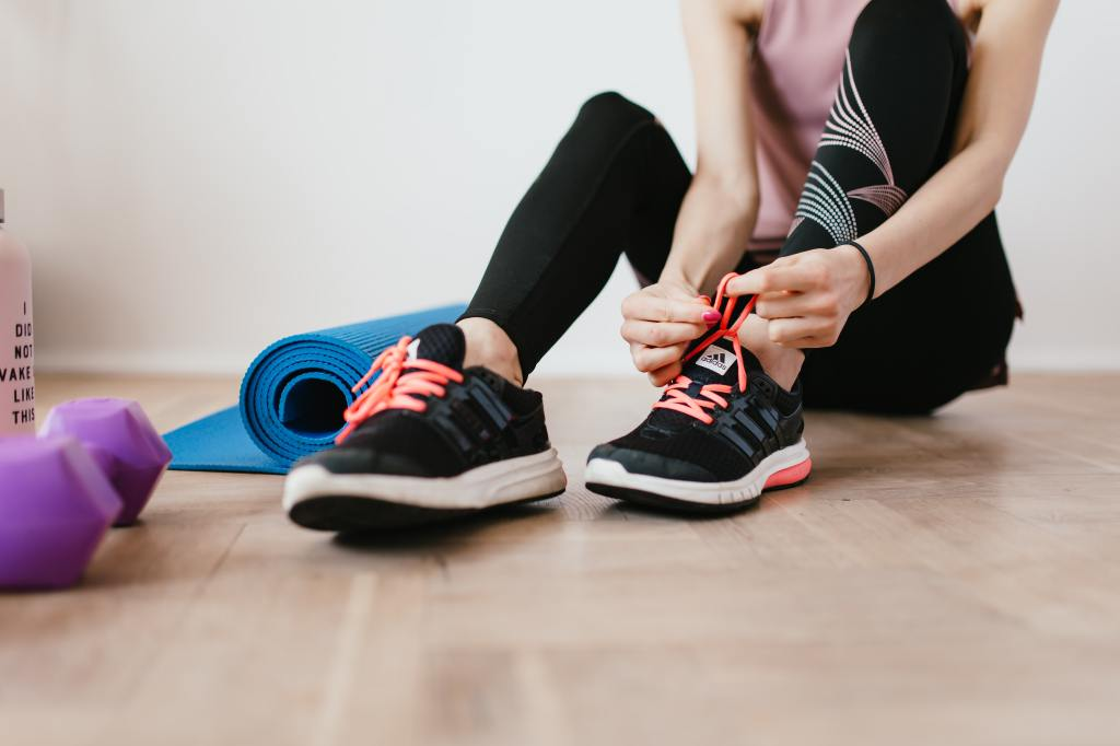 woman tying running shoes before exercising